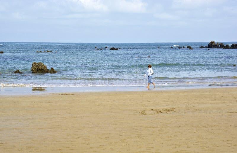 Noja, Spain - April 2nd 2015: Woman walks along the beach of Noja, Cantabria royalty free stock image