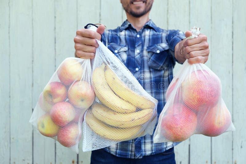 Nollf?rlorat shoppingbegrepp Le mannen som rymmer återvinningsbara ecopåsar med nya frukter Enkel bruksplast- f?r f?rbud royaltyfri bild