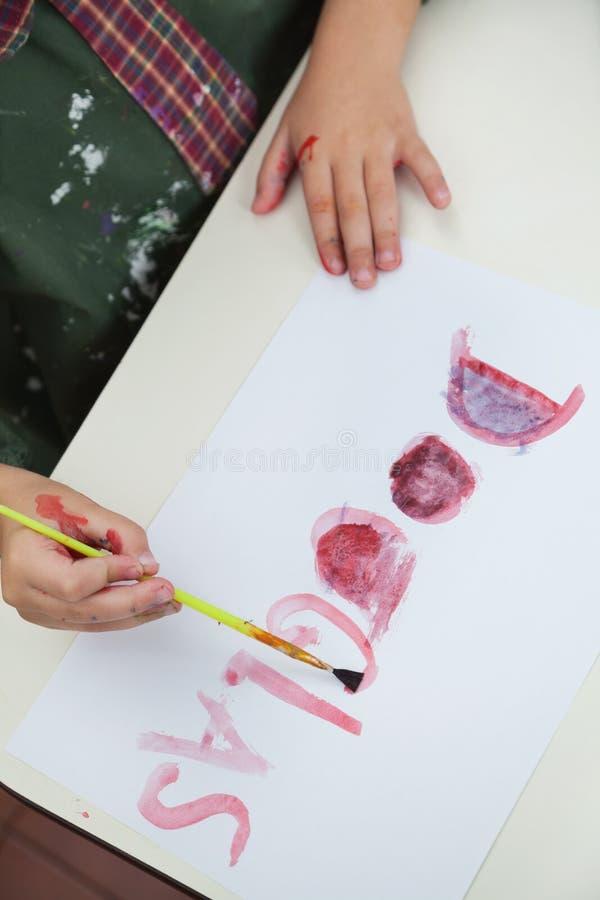 Nom de peinture de garçon sur le papier en Art Class photo stock