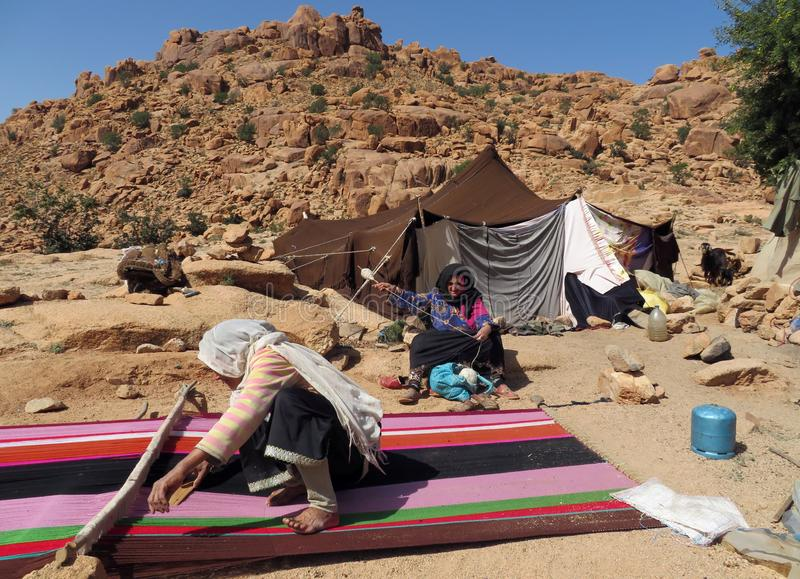 Nomade berber vrouwen die tapijten voor hun tent in de bergen weven stock afbeeldingen