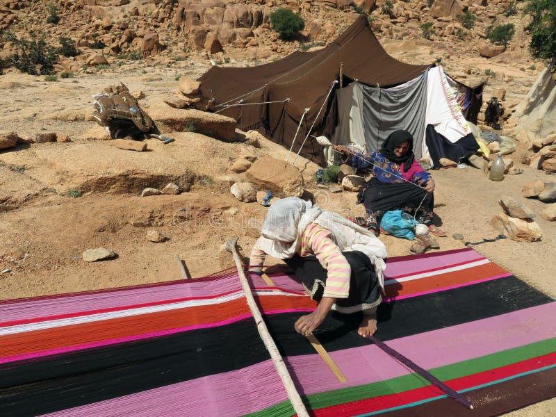 Nomade berber vrouwen die tapijten voor hun tent in de bergen weven stock afbeelding