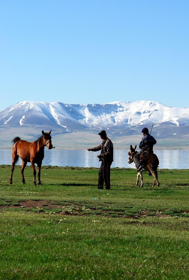 Nomadi del Kirghizstan sui cavalli fotografia stock libera da diritti