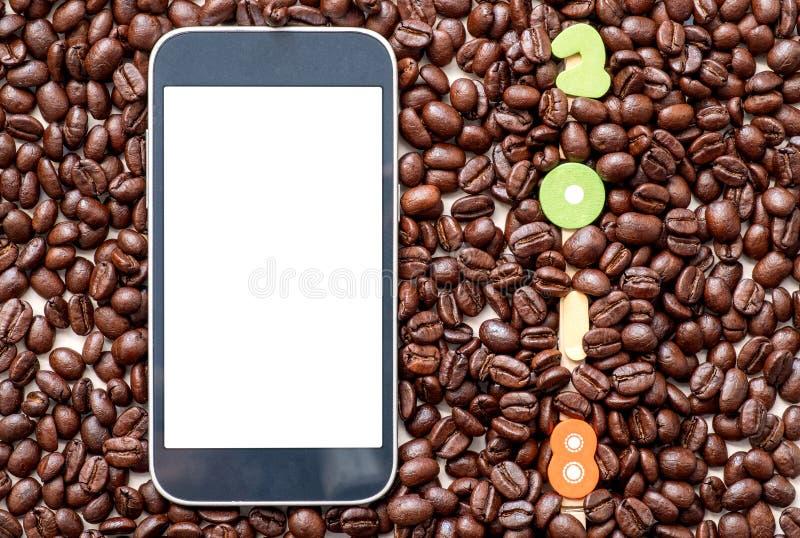 Nombre 2018 à l'arrière-plan de grains de café et téléphone intelligent sur le le images libres de droits