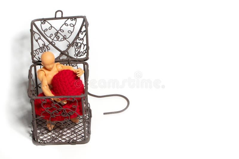 Nombre d'actions se reposant dans la cage et tenant le coeur rouge sur le fond blanc Concept de l'amour et de l'emprisonnement photographie stock libre de droits