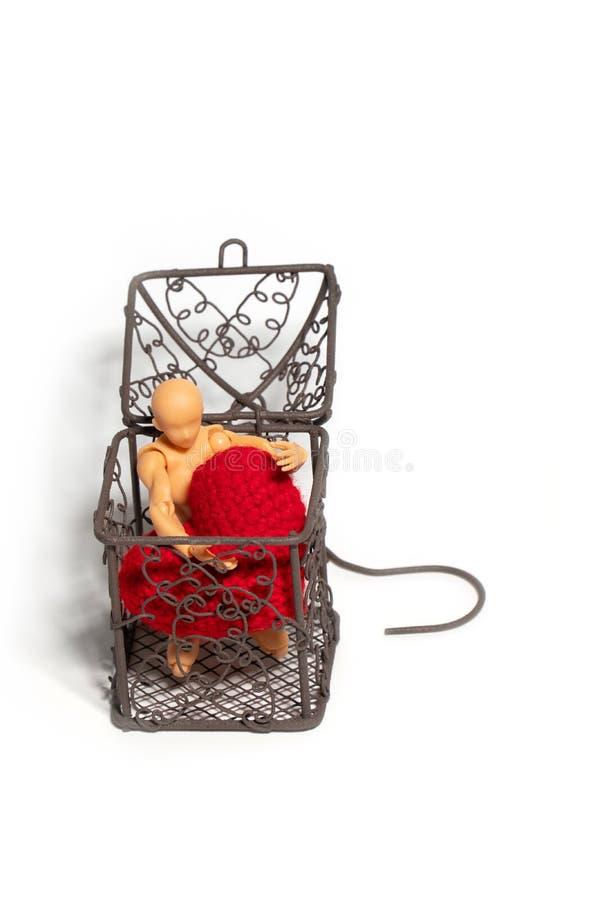Nombre d'actions se reposant dans la cage et tenant le coeur rouge sur le fond blanc Concept de l'amour et de l'emprisonnement image stock