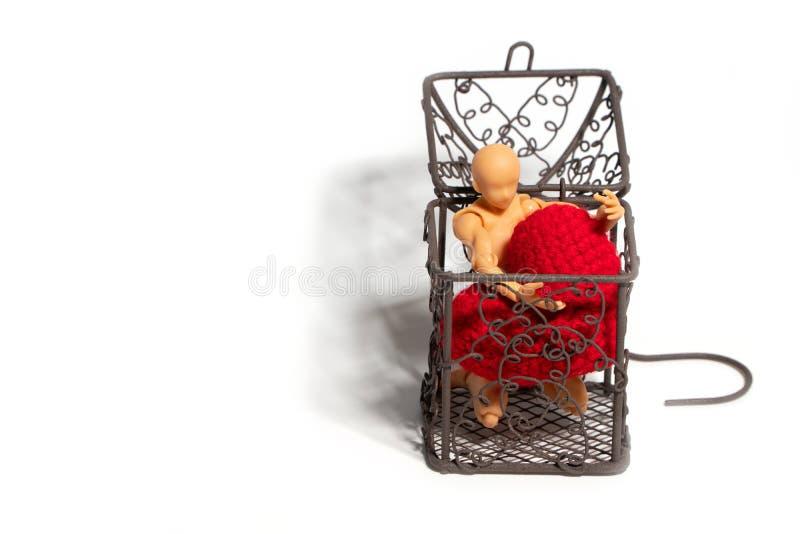 Nombre d'actions se reposant dans la cage et tenant le coeur rouge sur le fond blanc Concept de l'amour et de l'emprisonnement images stock