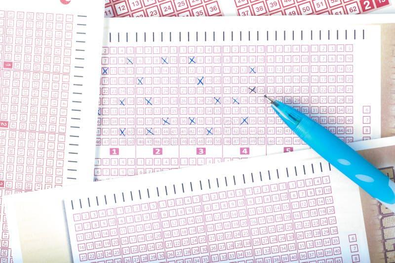Nombre d'inscription de main du ` s de personne sur le billet de loterie avec le stylo gain photos libres de droits