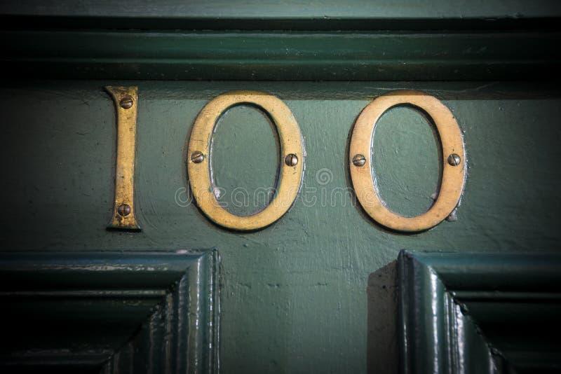 Nombre de porte de laiton du numéro cent sur la porte peinte superficielle par les agents image libre de droits