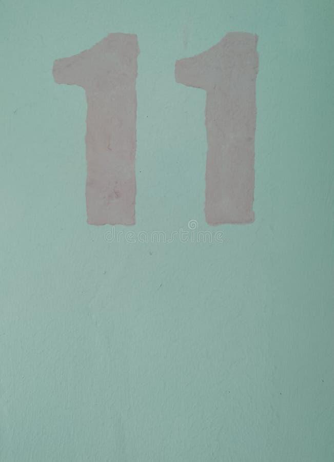 nombre 11 dessiné par la peinture de rose de pochoir sur un tir étroit de plan rapproché bleu-clair de fond illustration de vecteur