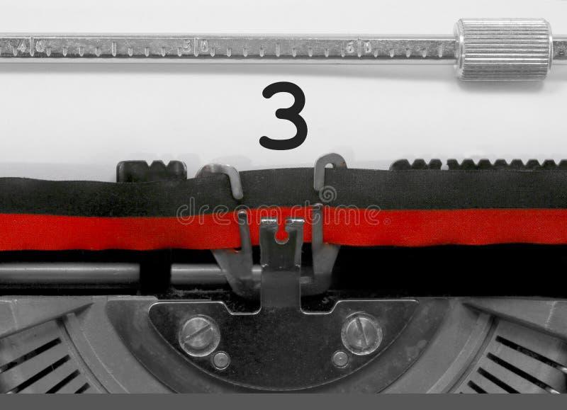 Nombre 3 par la vieille machine à écrire sur le livre blanc images stock
