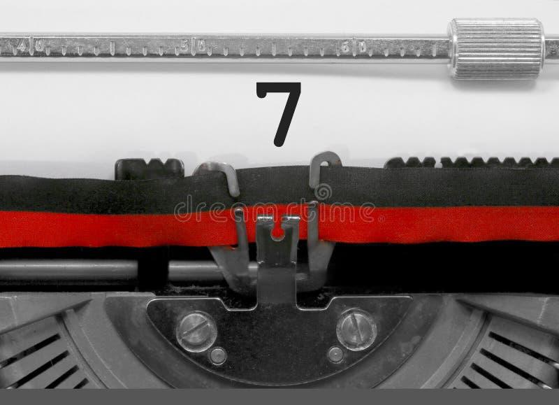Nombre 7 par la vieille machine à écrire sur le livre blanc photos stock