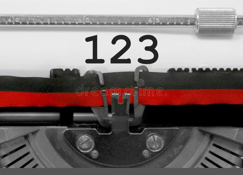 Nombre 123 par la vieille machine à écrire sur le livre blanc images stock