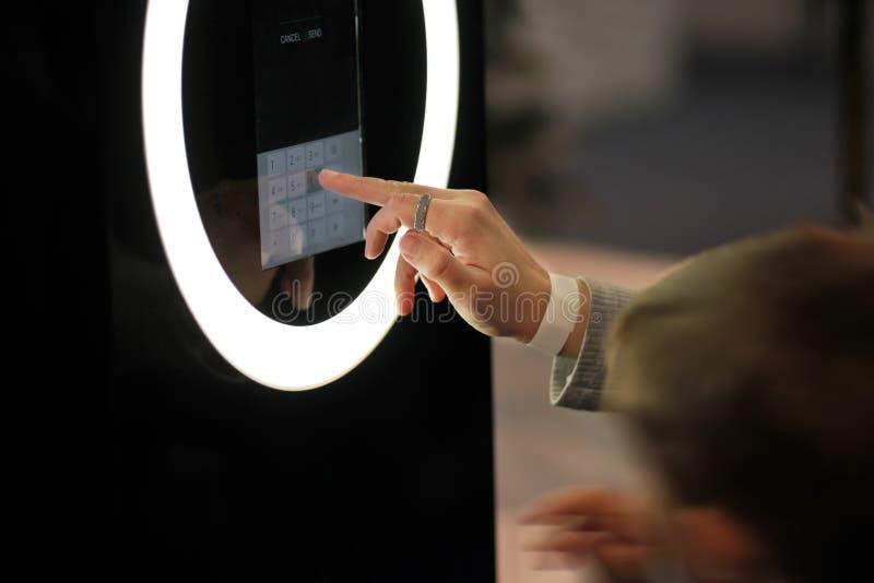 Nombres de composition de main du ` s de femme sur un écran tactile numérique rougeoyant d'un terminal dans le centre commercial photographie stock libre de droits