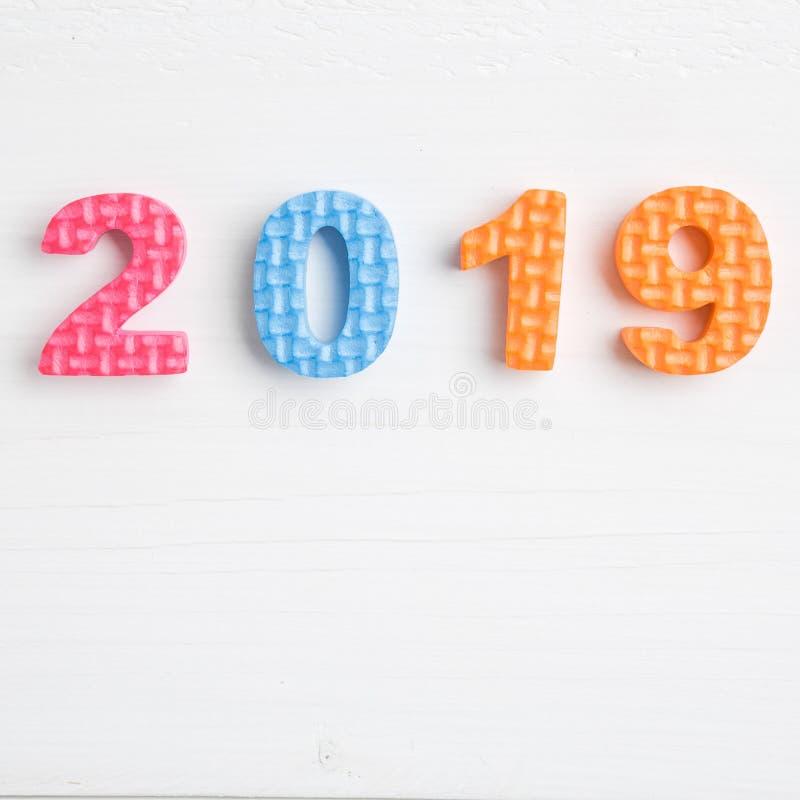 Nombres de mousse de jouet de couleur en 2019 sur la surface en bois lumineuse image stock