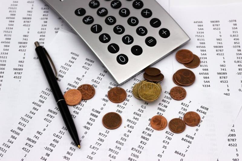 Nombres sur le papier, un stylo et une calculatrice, pièces de monnaie photographie stock