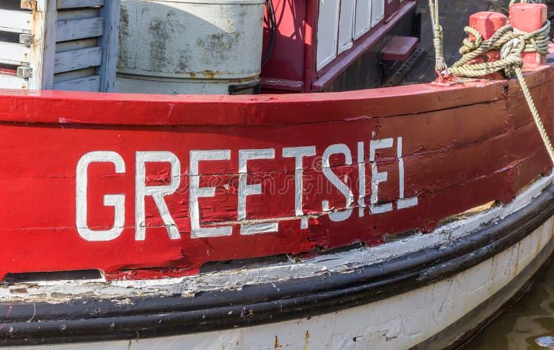 Nome da vila em um barco de pesca de madeira vermelho em Greetsiel fotografia de stock