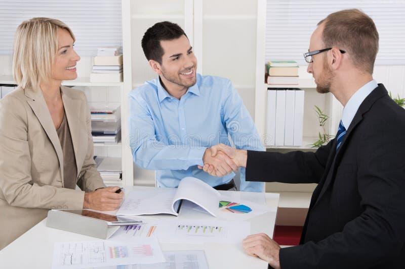 Nomeação do cliente: equipe do negócio com o cliente que faz o aperto de mão imagens de stock royalty free