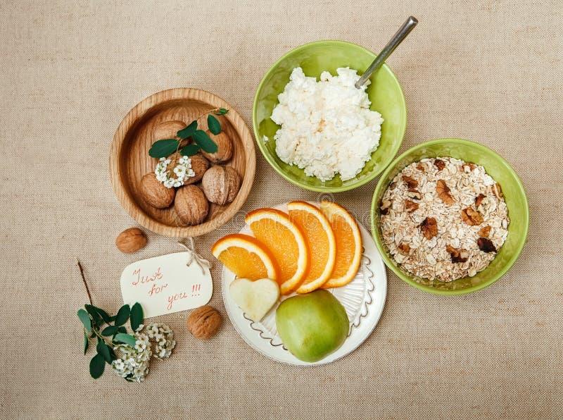 Nomeações de tabela para BreakfastWalnuts orgânico saudável, farinha de aveia e requeijão Corte a laranja e o Apple Cerâmico e de fotografia de stock royalty free