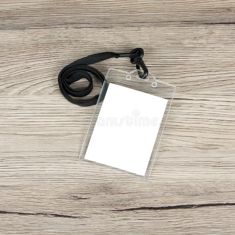 Nomini il distintivo della carta di identificazione con cavo su fondo di legno immagine stock