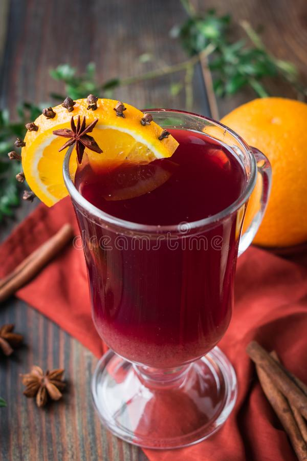 Non-alcoholic mulled wine from grape juice with orange and spices in a glass goblet. Non-alcoholic mulled wine from grape and orange juice with cloves and star royalty free stock images