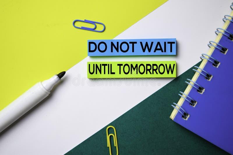 Non aspetti fino al testo di domani sulle note appiccicose con il concetto della scrivania fotografie stock libere da diritti