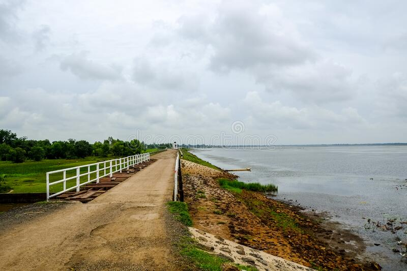 Non-asphalt road in upcountry Buriram, Thailand. With lake and long way royalty free stock photography
