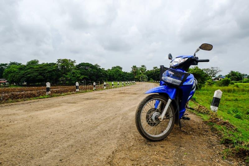Non-asphalt road in upcountry Buriram, Thailand. Blue motorcycle on Non-asphalt road in upcountry Buriram, Thailand royalty free stock photo