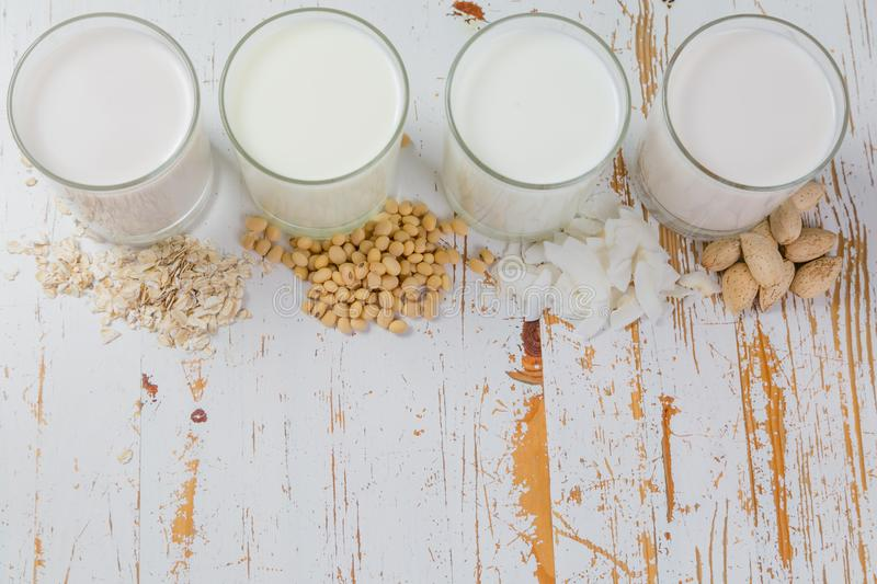 Non-dairy milk alternatives. In glasses on white wood background royalty free stock photos