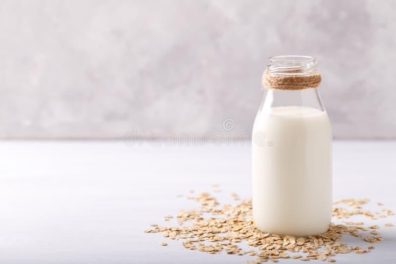 Non dairy oat milk. Vegan non dairy oat milk and flakes on white wooden background stock photo