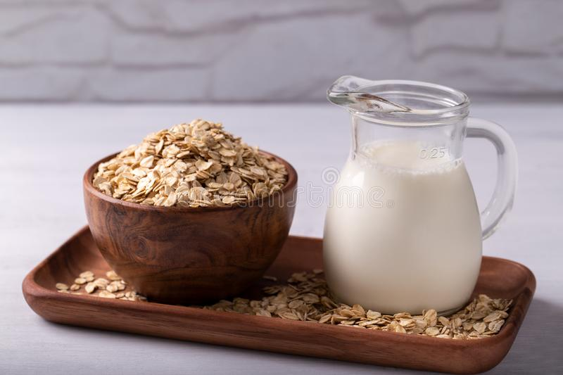 Non dairy oat milk. Vegan non dairy oat milk and flakes on white wooden background. Healthy eating stock photos