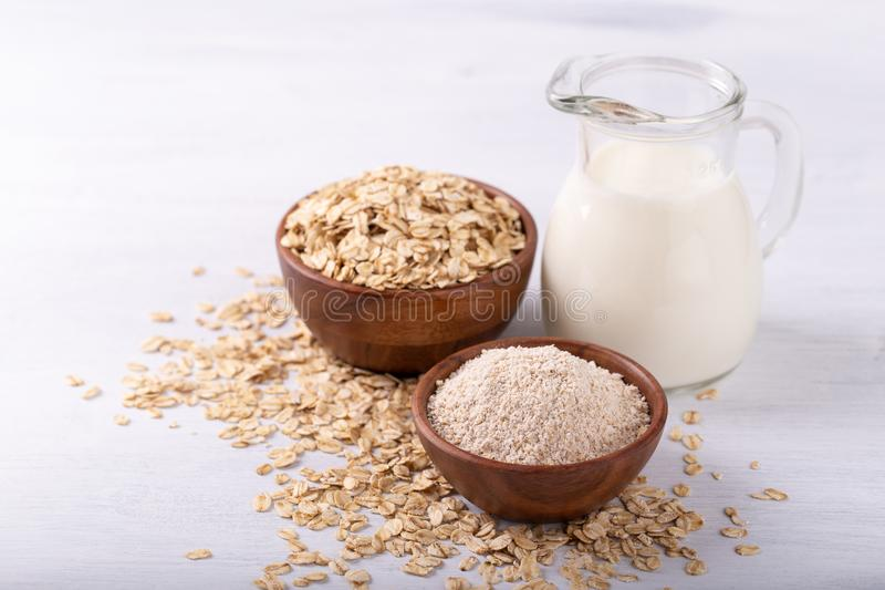 Non dairy oat milk. Vegan non dairy oat milk,flour and flakes on white wooden background. Healthy eating stock image