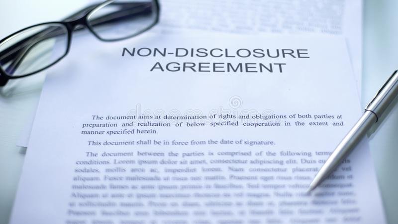 Non-disclosure agreement lying on table, pen and eyeglasses on official document. Stock photo royalty free stock photography