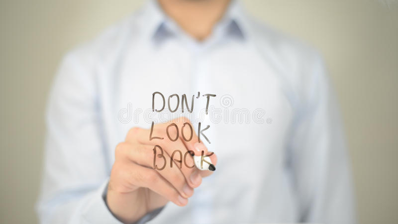 Non guardi indietro, scrittura dell'uomo sullo schermo trasparente immagine stock