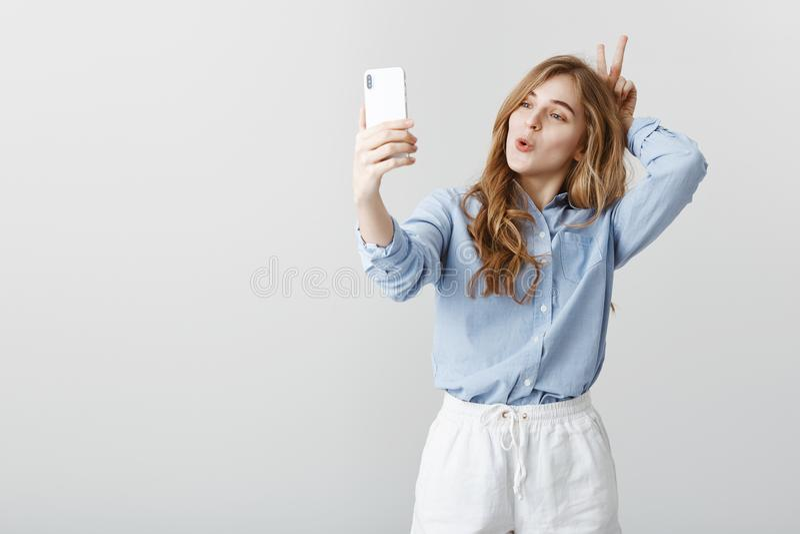 Non honteux pour être drôle devant l'appareil-photo Fille féminine positive belle avec les cheveux blonds dans le chemisier bleu, image stock