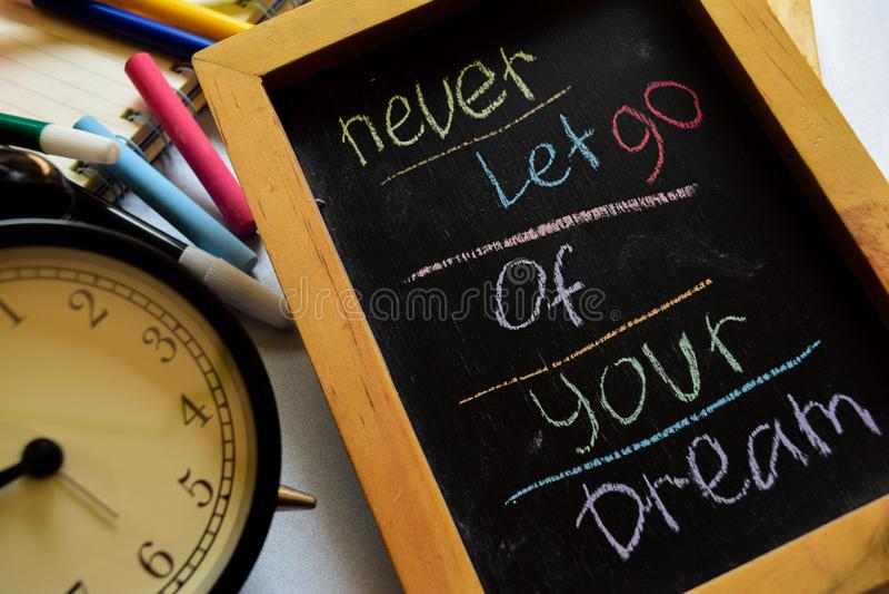 Non lasciato andare mai del vostro sogno su scritto a mano variopinto di frase sulla lavagna, sulla sveglia con la motivazione e  immagine stock