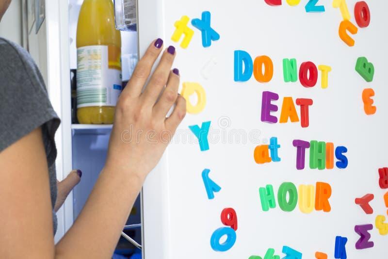 Non mangi a quest'ora il messaggio sul frigorifero bianco scritto con le lettere magnetiche variopinte, concetto di dieta fotografie stock