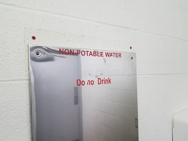 Non-potable water do not drink sign on bathroom mirror. Non-potable water do not drink sign on bathroom or restroom mirror stock photos