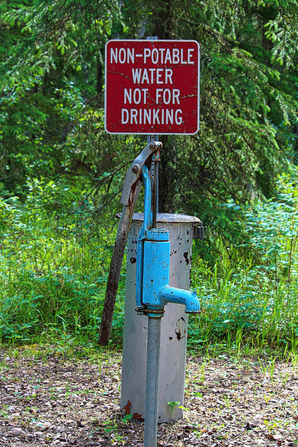 A non-potable water, not for drinking sign near a pump.  stock photography