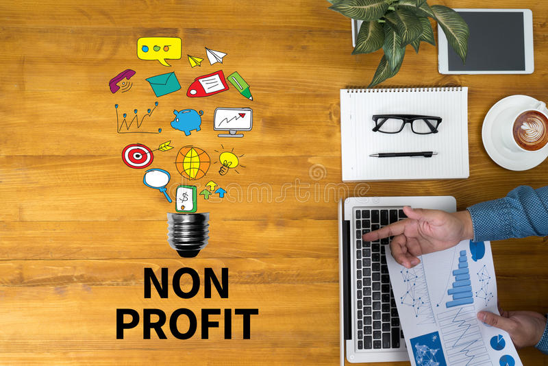 NON PROFIT. Businessman working at office desk and using computer and objects, coffee, top view, with copy space stock image