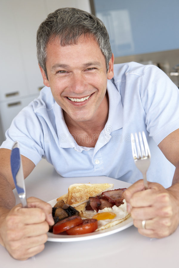 non sano centrale invecchiato dell'uomo fritto mangiare della prima colazione fotografia stock libera da diritti