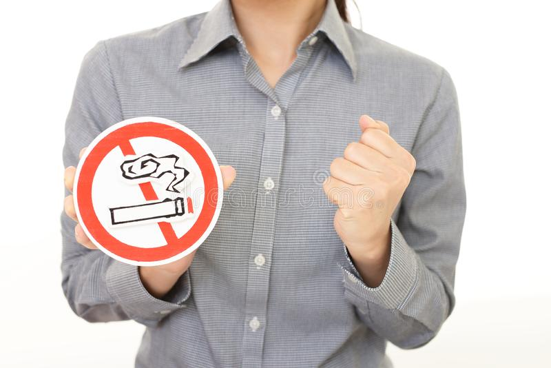 Non smoking sign. Woman holds non smoking sign royalty free stock image