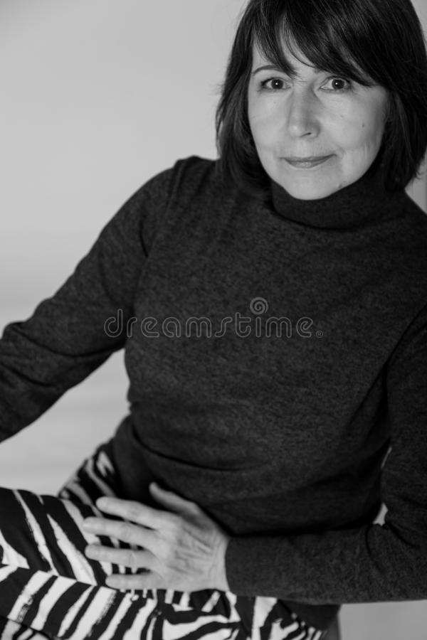 Non-standard monochrome view. Portrait old woman with mysterious smile. Strange look. Black and white portrait of woman without retouching sitting on bright royalty free stock photography