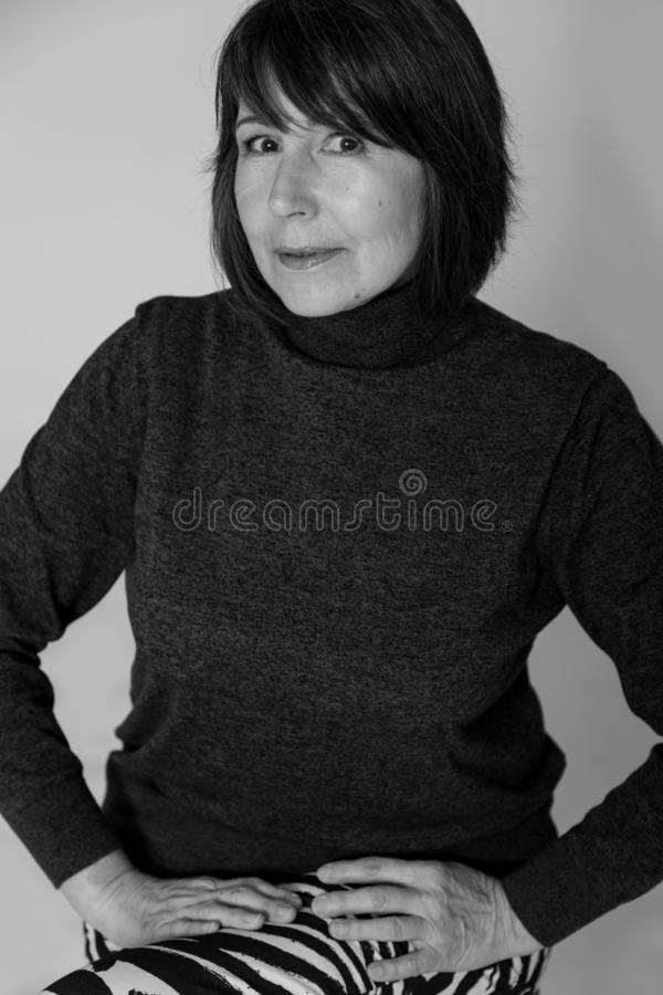 Non-standard monochrome view. Portrait old woman with mysterious smile. Strange look. Black and white portrait of woman without retouching sitting on bright stock image