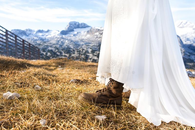 Non-standard shoes for the bride. Wedding in the Alps mountains royalty free stock photo