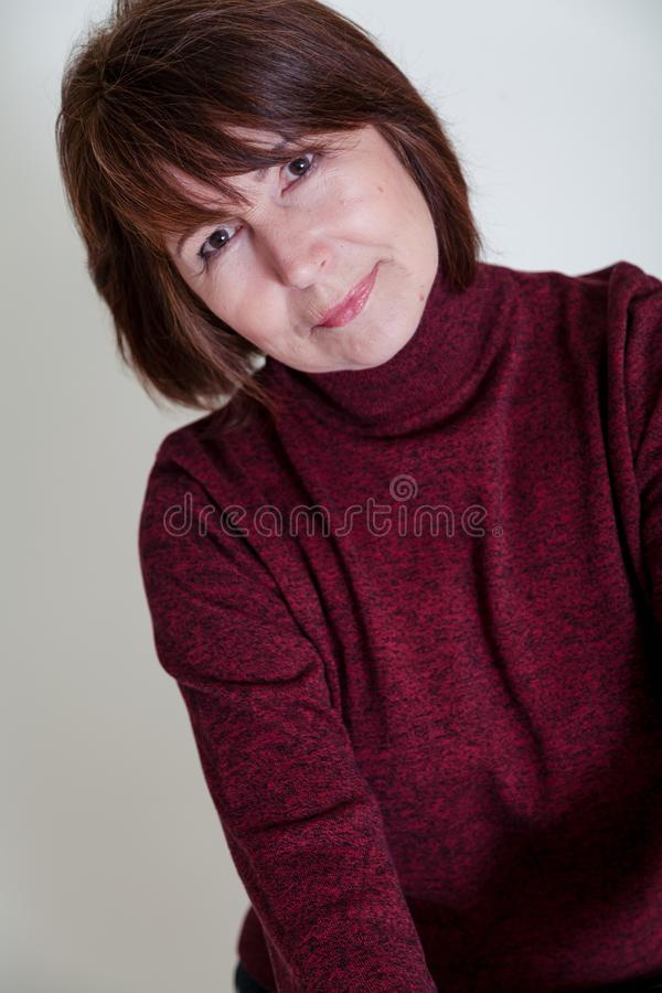Non-standard view. Portrait of old woman with mysterious smile. Strange look. Portrait of a woman without retouching sitting on a bright monophonic background royalty free stock images