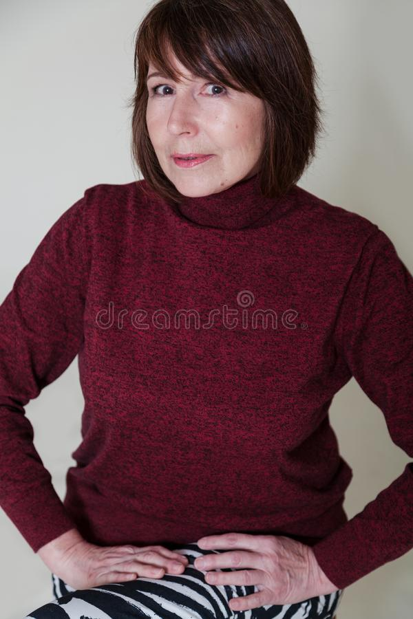 Non-standard view. Portrait of old woman with mysterious smile. Strange look. Portrait of a woman without retouching sitting on a bright monophonic background stock photos