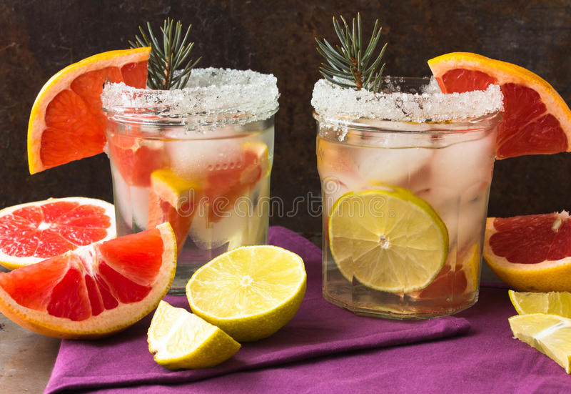 Nonalcoholic drinkcoctail av nya frukter: grapefrukt limefrukt, rosmarinbegrepp av en sund drink rostig bakgrundsmetall Två ca arkivfoton