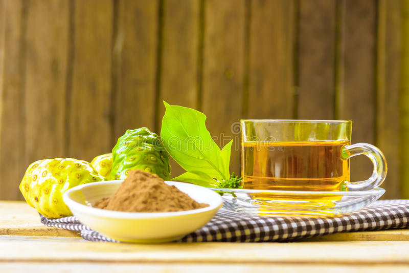 Noni erval quente, suco erval de Noni com fruto do noni e pó do noni no fundo de madeira fotografia de stock