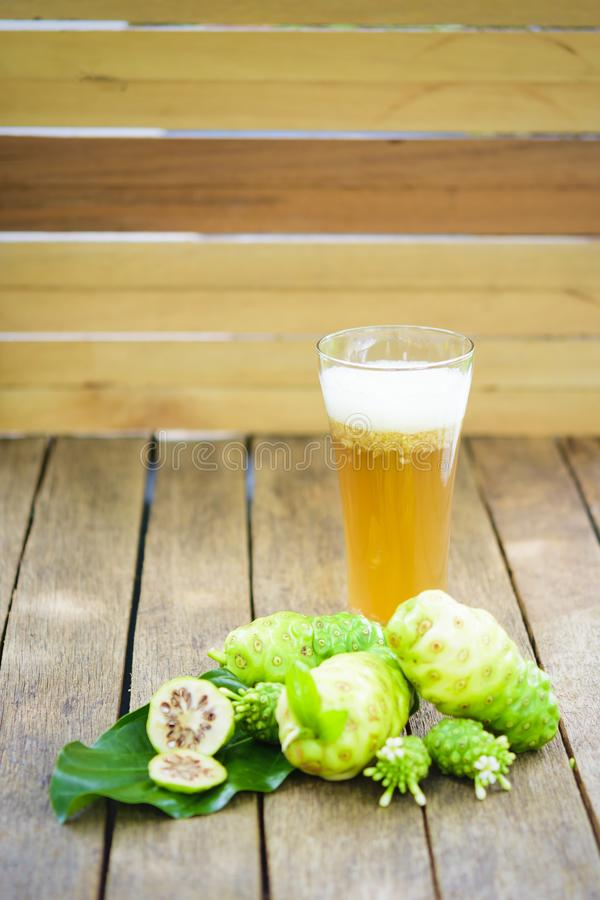 Free Noni Fruit And Noni Juice And Blossom On Old Wooden Table.Vertical. Royalty Free Stock Images - 106703379