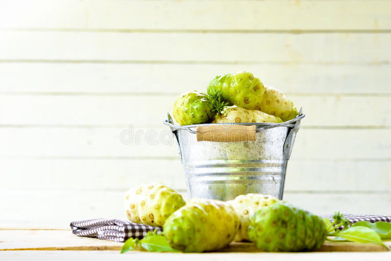 Noni fruit in zinc bucket and noni on table on white wooden background. stock images